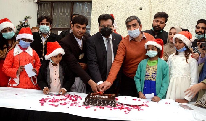rovincial Minister for Minority Affairs Ijaz Alam Augustine cutting the Christmas cake during his visit at Sundas Foundation