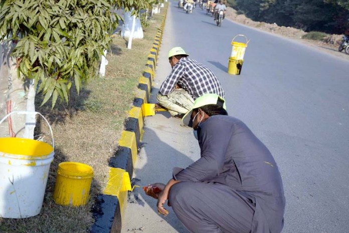 Laborers are busy in coloring green belt at Jail road