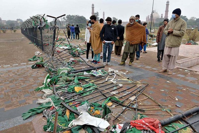 People standing near the broken fence at Greater Iqbal Park after last night PDM public meeting