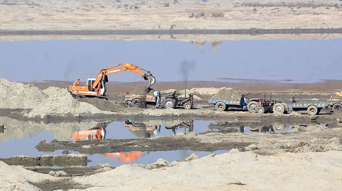 Labourer loading sand on tractor trolley from the dry bed of River Chenab near head Muhammad Wala