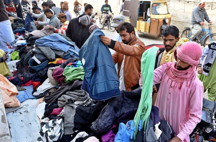 People selecting and purchasing old clothes from vendor at Press Club Road