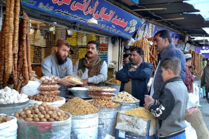 People busy in purchasing dry fruits from vendor at Meezan Chowk as demands increased due to cold weather