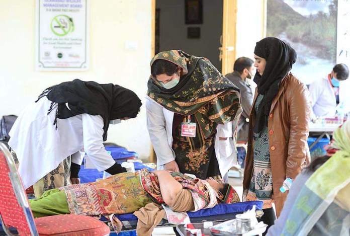 A woman donates blood during an awareness hike for Thalassemics organised by Sultana Foundation at Trail -5 in the federal capital