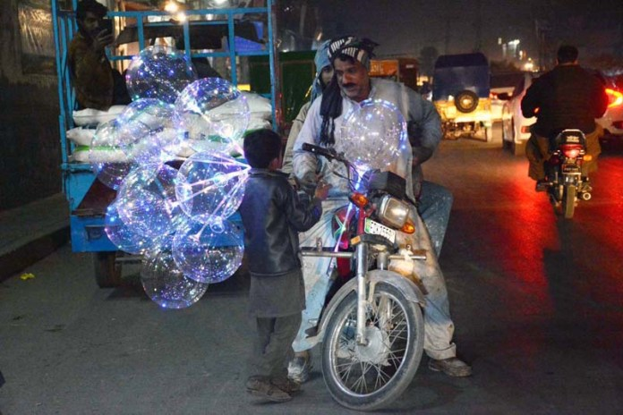 A young vendor selling balloons decorating with lights to customer