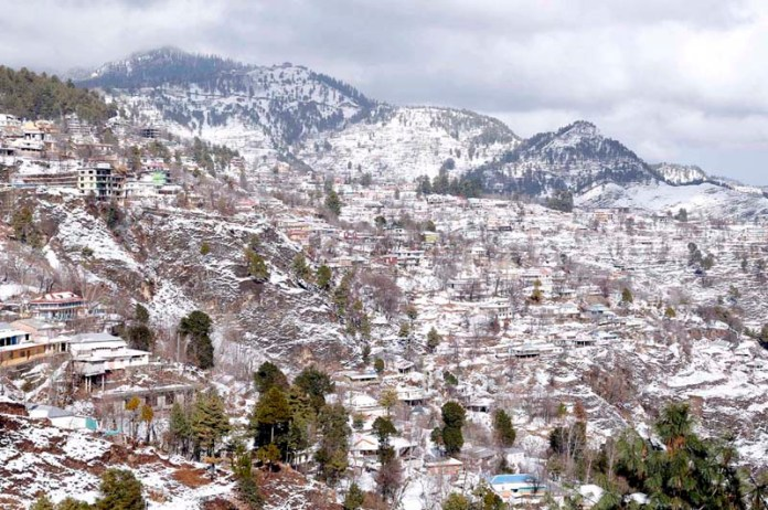 A view of hilly resort covered by first snowfall of 2021 in the town of Murree dipping the temperature
