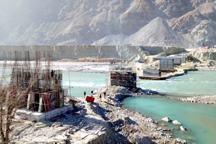 A view of under construction RCC bridge of Chilmishdas to Sultanabad on the River Hunza