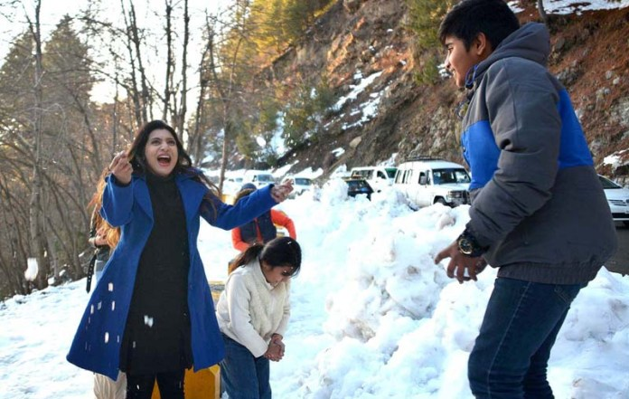 Visitors throwing snow balls at each other along the roadside in hilly town