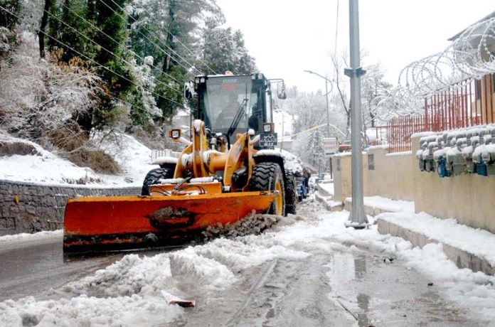 Heavy machinery busy to remove the snow to clear the road as the hilly resort is covered by the first snowfall of 2021 in the town of Murree