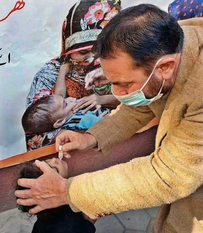 Health worker administering polio drop to child during 5-days anti polio campaign