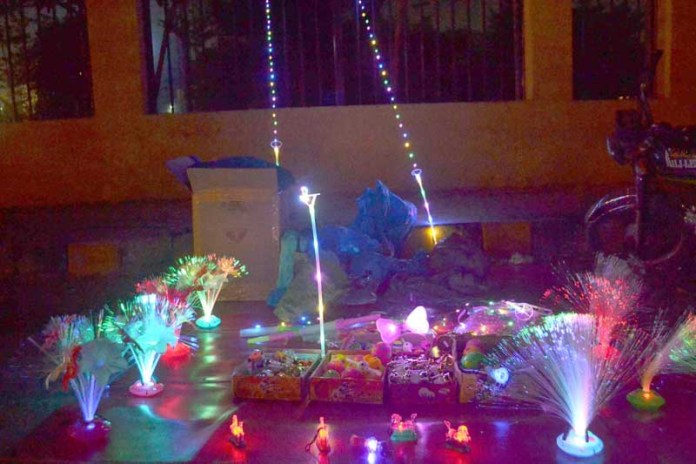Vendor displaying decorative colorful lighting lamp at roadside setup