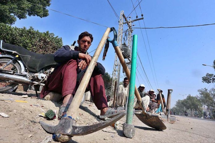 Labourers along with their tools waiting for daily job while sitting on roadside at Latifabad Chowk