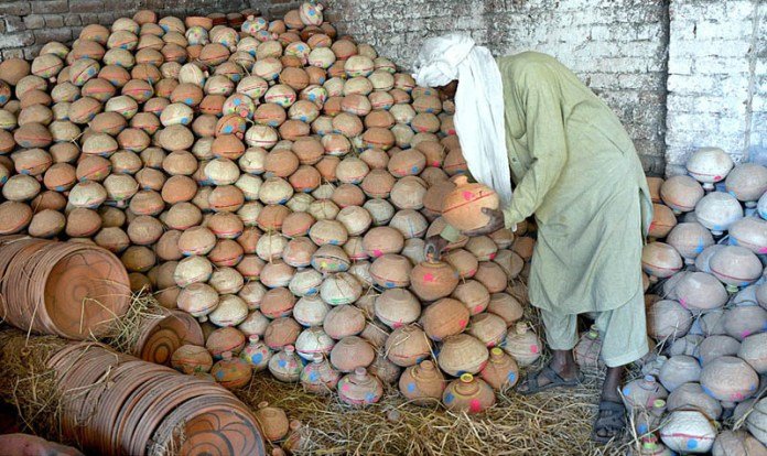 A shopkeeper busy in arranging and displaying clay made pots for customer