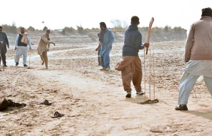 An aged man playing cricket with youngsters in Canal during the Annual Cleaning by Irrigation Department