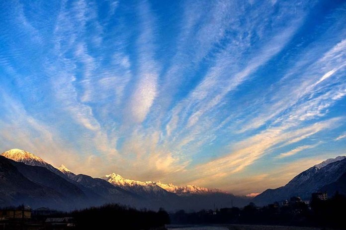 An attractive and eye-catching view of first sunrise of 2021 as a view of snow covered mountains along River Indus
