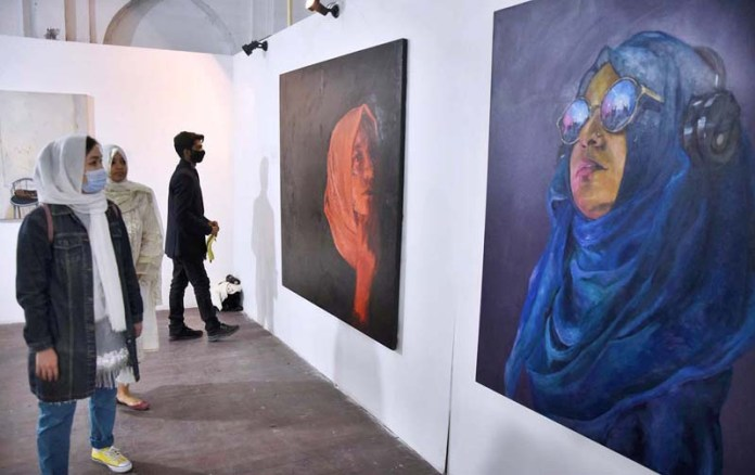 "Students viewing the displayed paintings during the Graduate Young Artists exhibition ""Degree Show BFA 2020"" of Visual Arts at Department of Fine Arts College of Art and Design University of the Punjab"