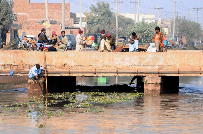 Workers of Irrigation Department busy in cleaning heap of garbage from Noubahar Canal