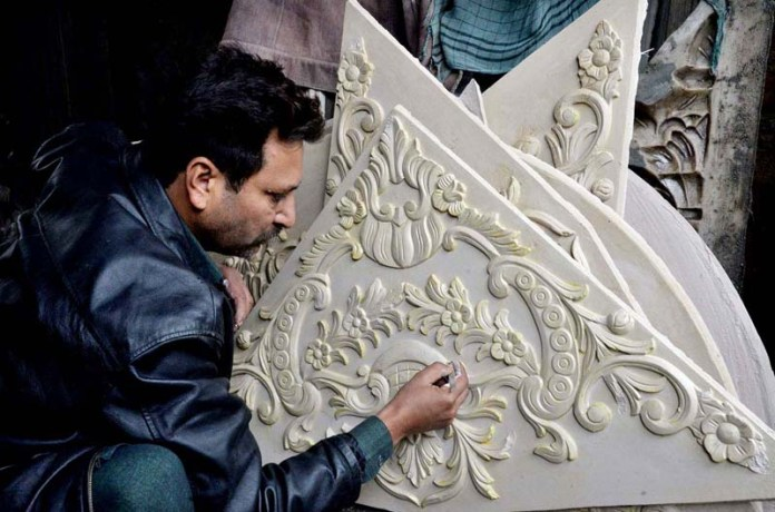 An artist designs on Plaster of Paris at his workplace
