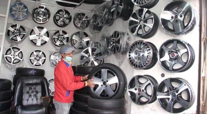 A worker busy in arranging rims to attract the customers at his workplace