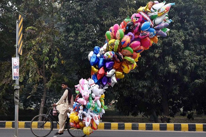 A street vendor on the way while displaying toy shaped gas filled balloons to attract customers at Canal Road in Provincial Capital
