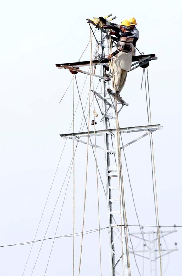WAPDA staffers busy in repairing electric wire on an electric pole at Swan Camp in the outskirts of the city