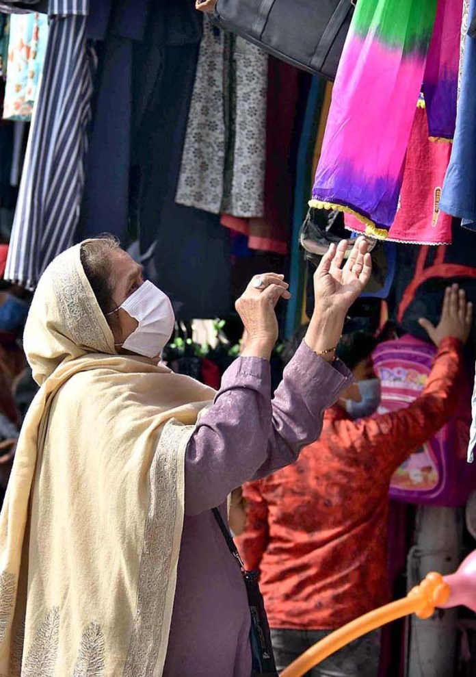 A female customer selecting clothes displayed by a vendor to attract the customers at weekly Friday Bazaar
