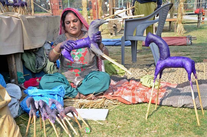 An artisan busy in preparing traditional decoration items for preparations of Spring Festival in Jilani Park