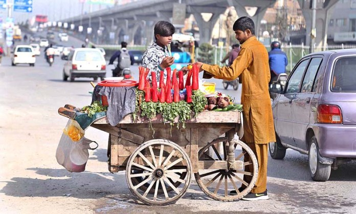 A customer purchasing radish and carrot from street vendor at Rehmanabad