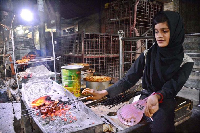 A young girl preparing traditional food for customers at roadside BBQ set-up in Korangi area to earn livelihood