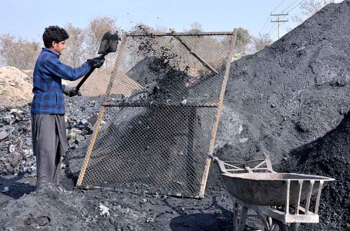 A gypsy youngster finding iron from waste of coal in front of Steel Factory
