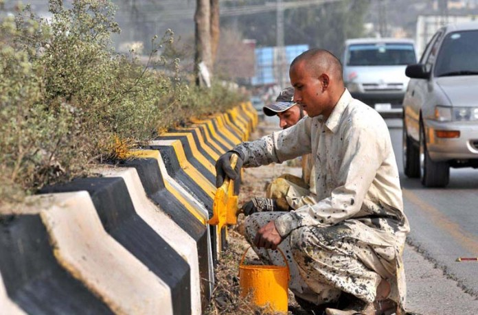 Labourers busy in paint the roadside cemented blocks along Murree Road near Rawal Lake