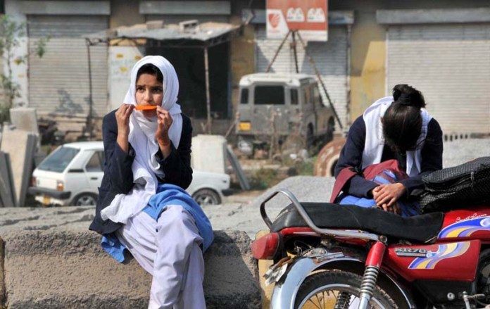 A student enjoying ice-cream while waiting for school bus at Murree Road, Bhara Kaho