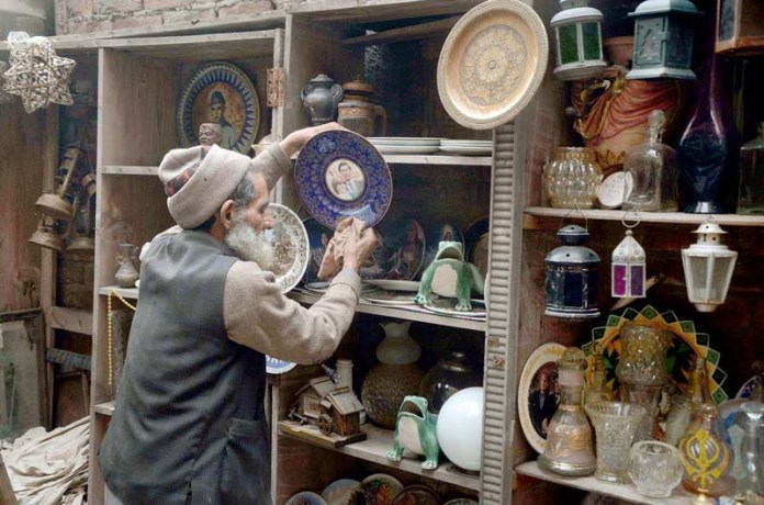 A shopkeeper dusting antique items at his shop to attract the customer