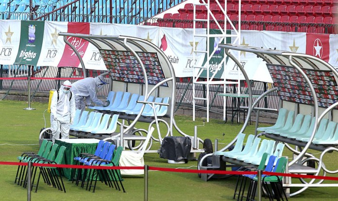 Staffers spraying and cleaning the player's dugout to ensure the disinfectant the COVID-19 virus before the start of Twenty20 cricket match between Pakistan and South Africa at the Gaddafi Cricket Stadium