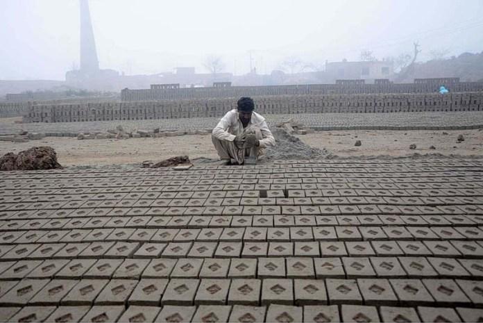 Labourer preparing raw bricks at kiln