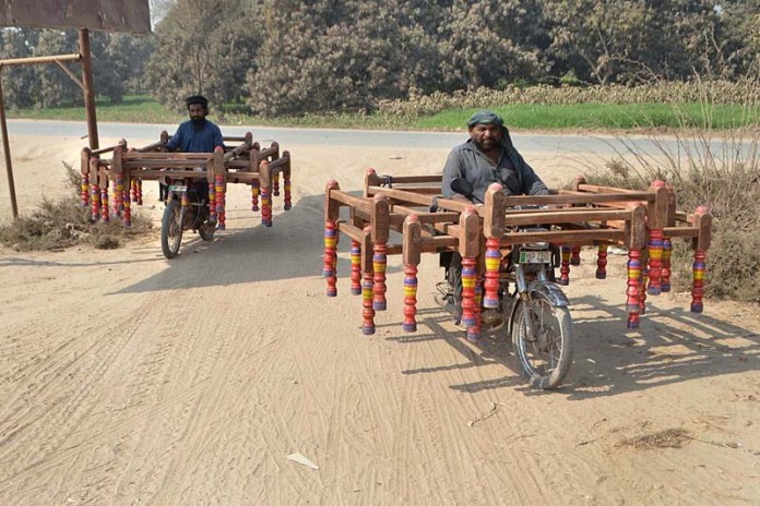 Motorcyclists on the way loaded with frames of traditional bed (Charpai) at Budhla Road