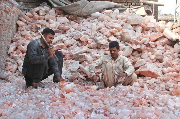 Labourers crushing salt into pieces at their workplace