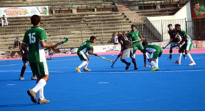 Players of Kashmir-IX and Green-IX struggling to get hold on the ball during an exhibition match to mark the Kashmir Solidarity Day played at National Hockey Stadium