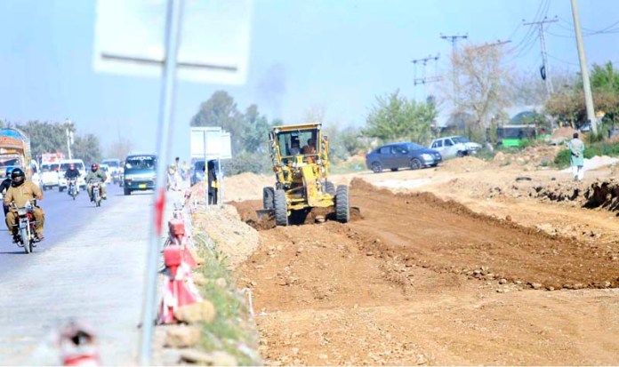 A view of heavy machinery working at a site to expand the Islamabad Expressway at PWD area in the city