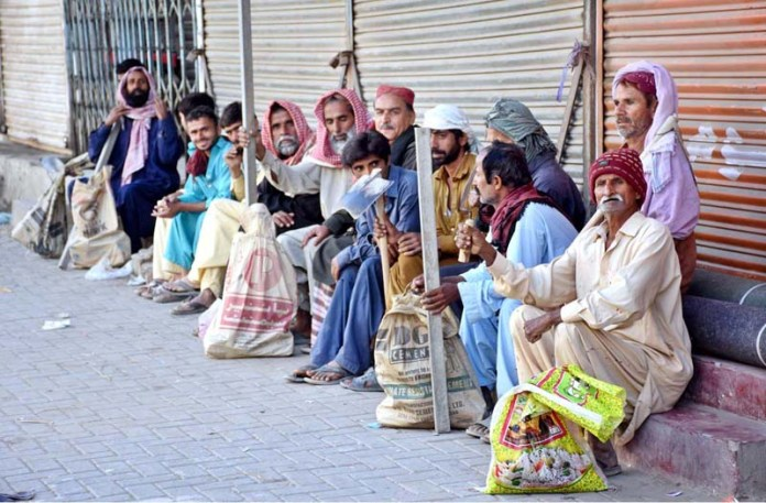 Labourers along with their tools waiting for daily job while sitting on roadside at Bandar Road