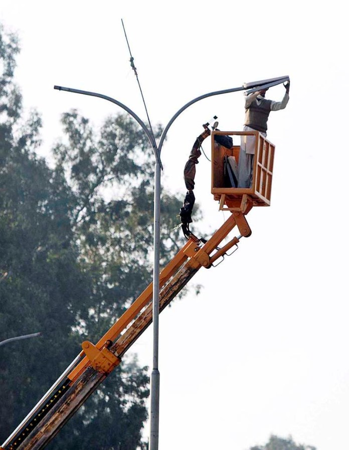 A WAPDA staffer busy in installing new streets lights at Chaklala