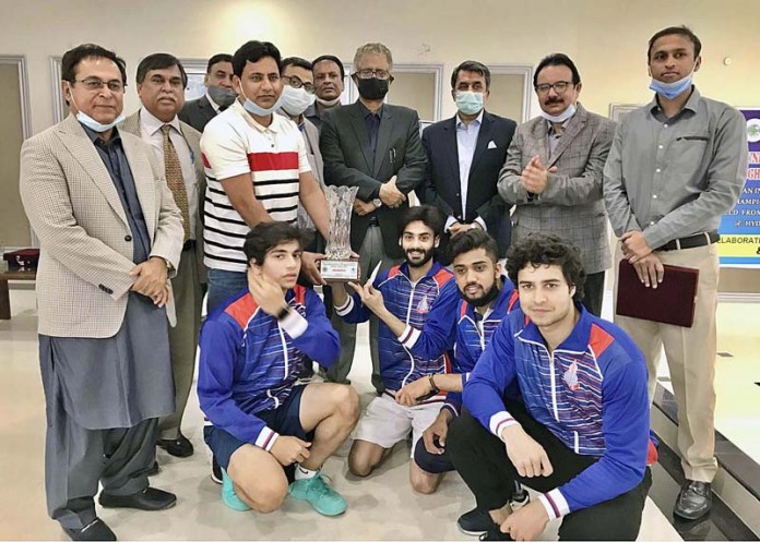 A group photograph of winning team of University of Central Punjab squash team with commissioner Muhammad Abbas Baloch during Pakistan Inter University Squash (Boys) Championship 2021 at Gymkhana Squash Court