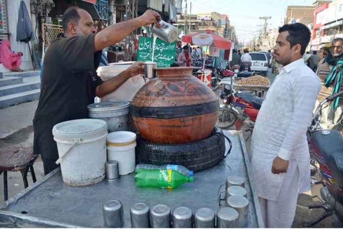 A vendor selling traditional summer drink lassi at Shaheen Chowk