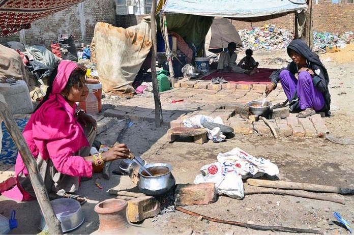 Gypsy women cooking food for her family in front of temporary hut at Latifabad