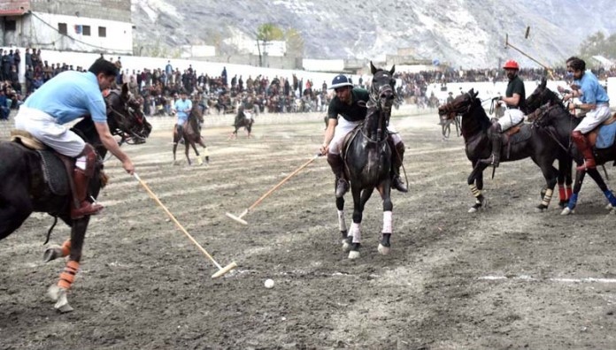 Players struggling to get hold on the ball in final polo match played between Gilgit Green and Gilgit Blue teams during Jashan-e-Baharan Polo Tournament at Shahi Polo Ground