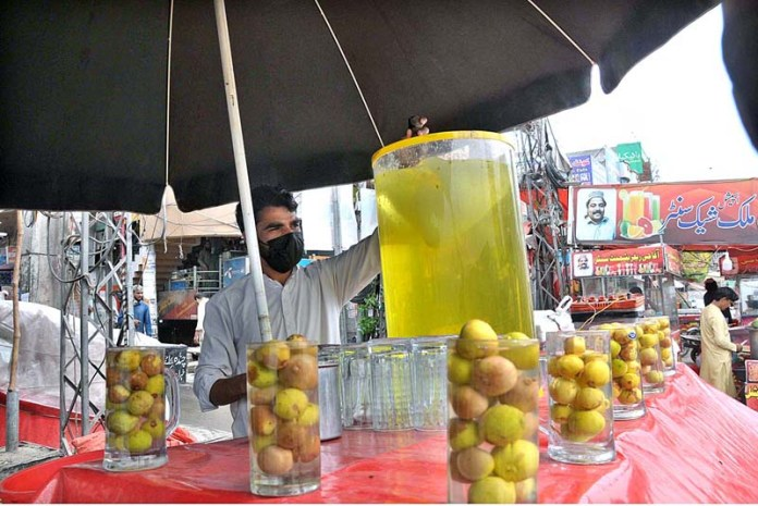 A vendor preparing traditional summer drink to attract the customers at his roadside setup in Federal Capital