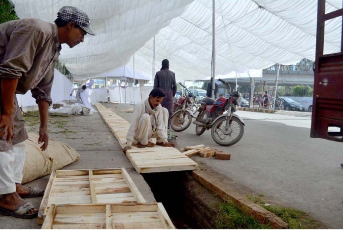 Labourers busy in covering open drain for setup Ramzan Bazaar in front of Company Bagh
