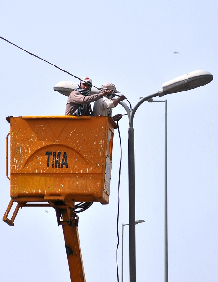 TMA staffers installing new electrical wires to connect with road lights near Vehari Chowk