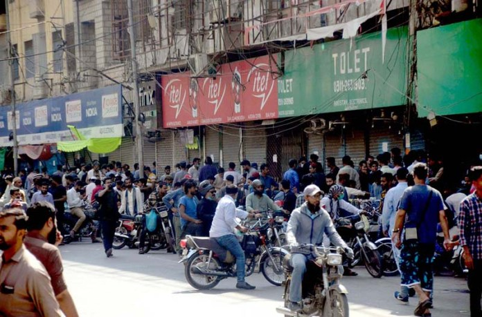 A large number of people in the market as vendors setup mobile phones accessories outside sealed Saddar mobile shops