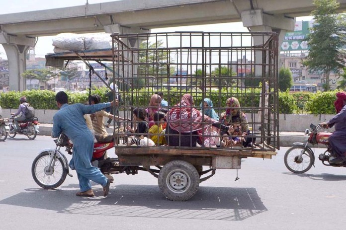 A family traveling by an out order caged tricycle rickshaw while the driver struggling to push it forward at Vehari Chowk
