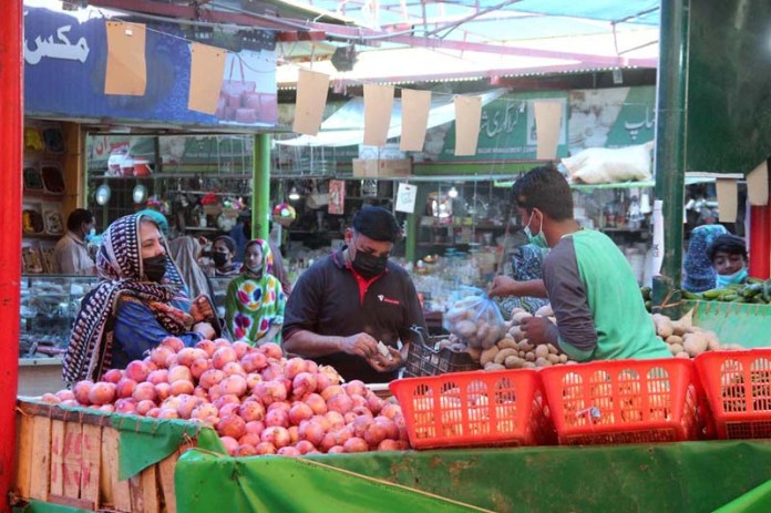 People purchasing vegetables on subsidized rates in a Sasta Ramzan Bazaar established at Wahdat Road